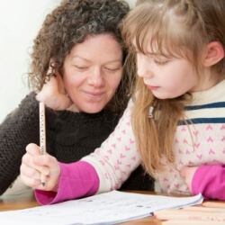 Mother helping her daughter with school work