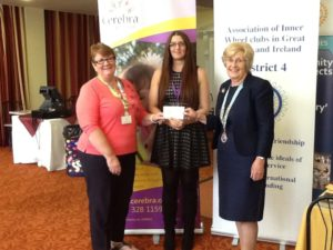 Cerebra's Annaleigh Williams picks up the cheque of proceeds from the fashion show from Edith Davison