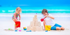 a boy and girl build a sandcastle