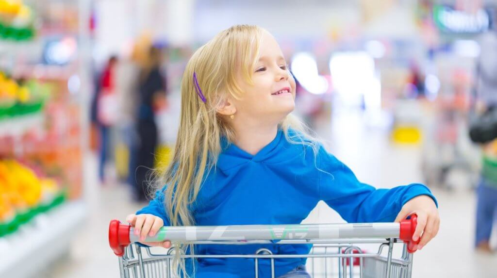 little girl in shopping trolley give as you shop