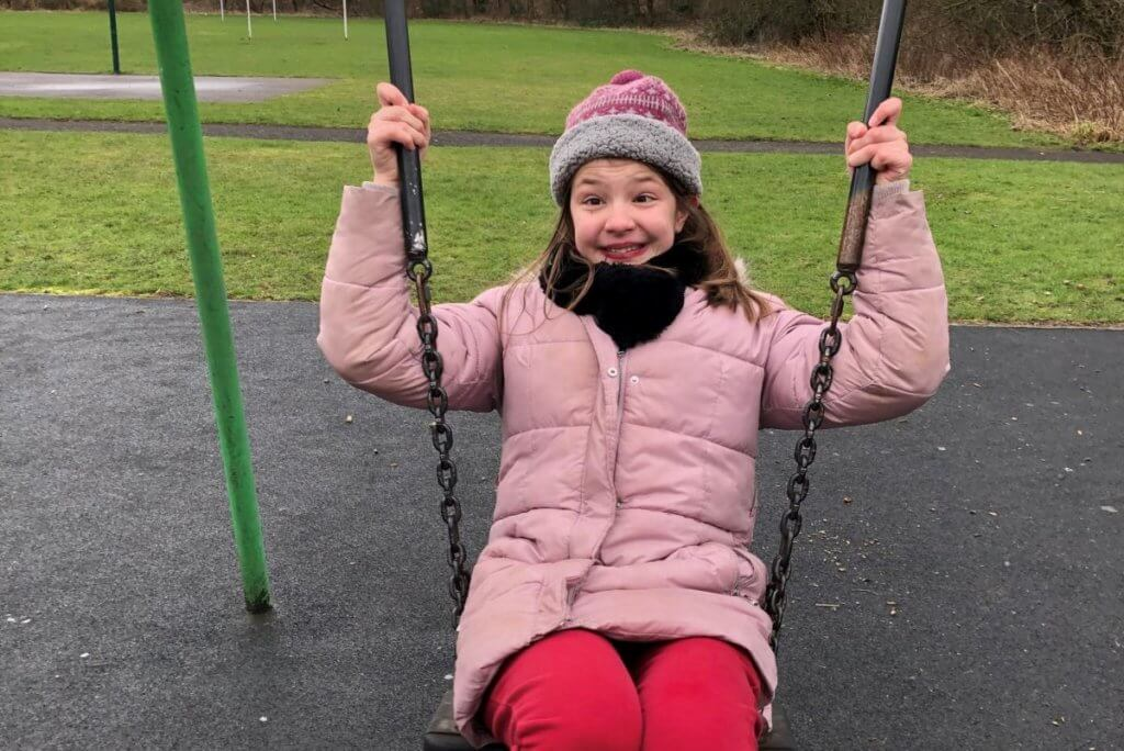rose smiling on a set of swings