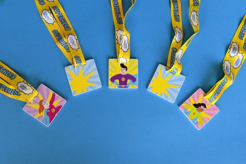 5 medals with a superhero theme arranged on a blue background