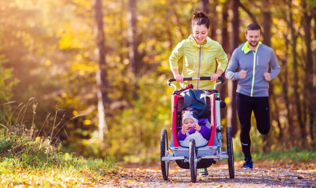 a woman jogging pushing a child in a running buggy, a man runs behind them