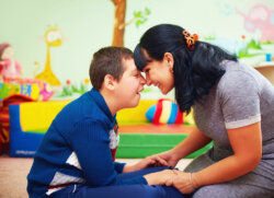 Boy with a female carer, smiling.