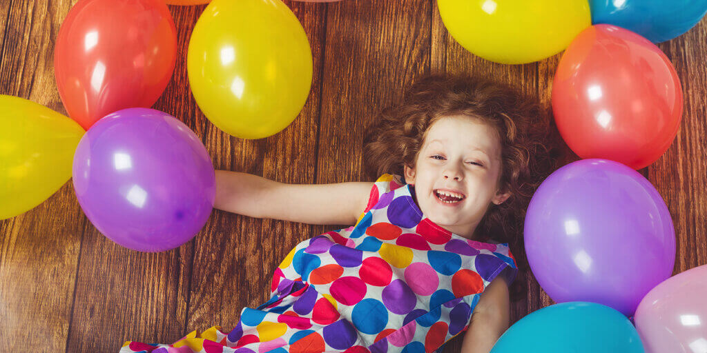 Girl surrounded by balloons, get involved in Cerebra charity for children with brain conditions.