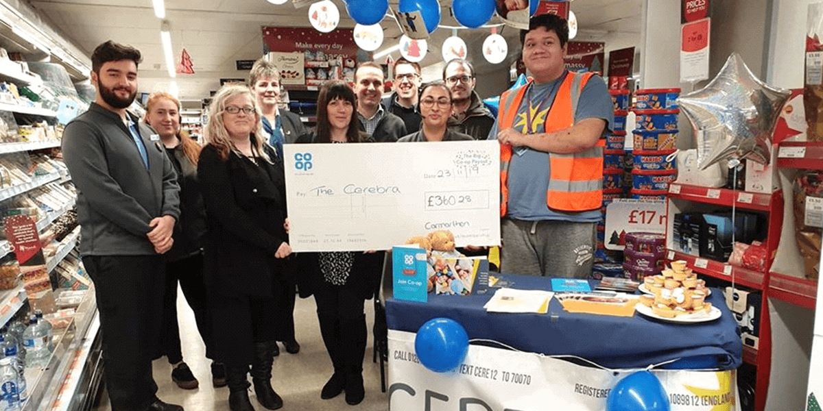 Samuel Turner collecting a cheque from Co Op
