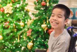 a smiling boy in a wheelchair in front of a christmas