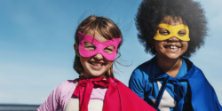 boy and girl dressed as superheroes smiling at the camera