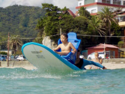 Child with brain condition on a adapted surfboard.